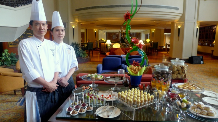 Chef Chan Eng Hua with his assistant posing with the buffet spread.