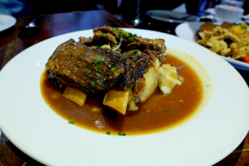 Wood fired oven roasted beef ribs in a reduction of red wine sauce on a  bed of mashed potato