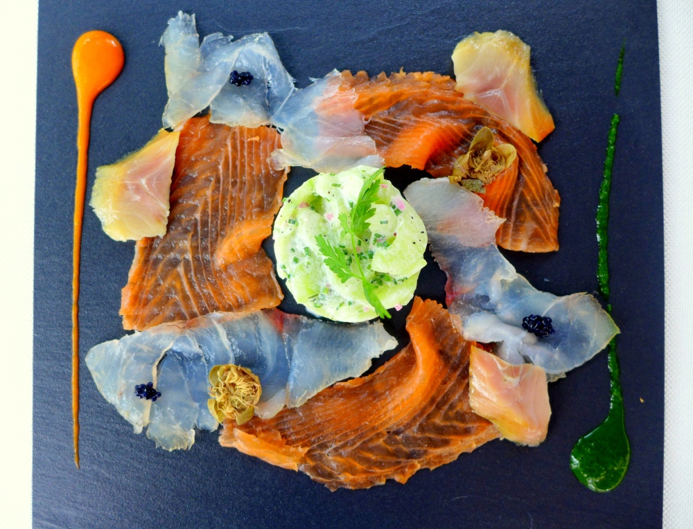 Homemade smoked fish platter, salmon, herring, sea bass  with  cucumber salad  and champagne vinegar