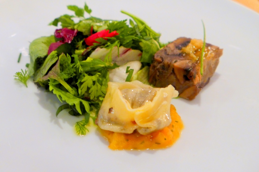 Roasted portobello pave with smoked garlic vinaigrette, mushroom tortellini with tomato fondue and herb salad